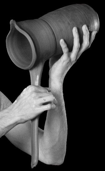 pulling the handle on a pitcher in our pottery studio